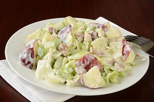 A plate of Waldorf salad on a simple wood background