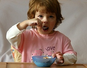 Child eating cereal for breakfast.