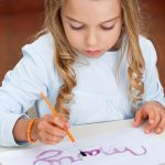 Little girl painting name on paper at desk in classroom