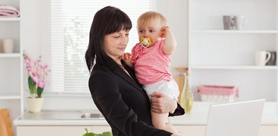 Beautiful brunette woman in suit holding her baby in her arms wh
