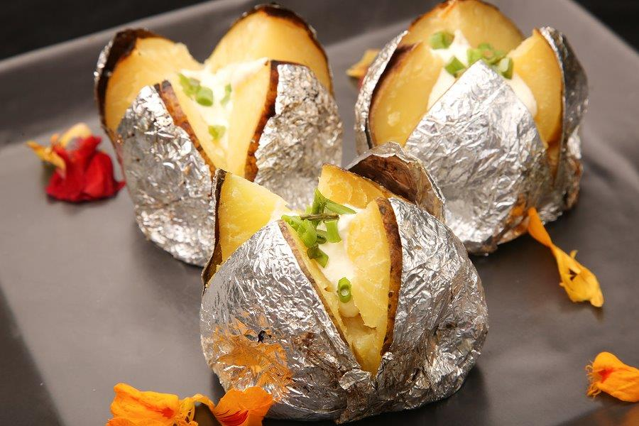 Spuds in the oven in foil and served with cheese and Greek yoghurt