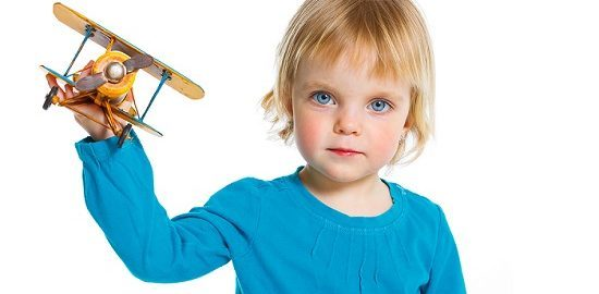 Cute little girl playing with a toy airplane